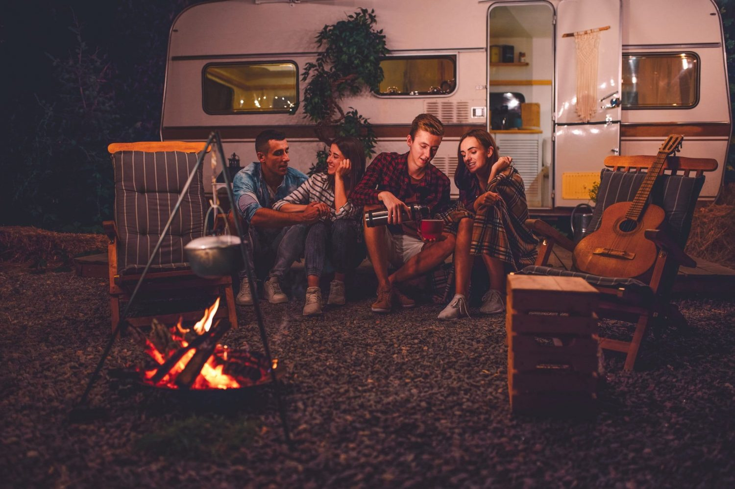 Four people sit around a campfire on their RV road trip vacation to the Oregon coast