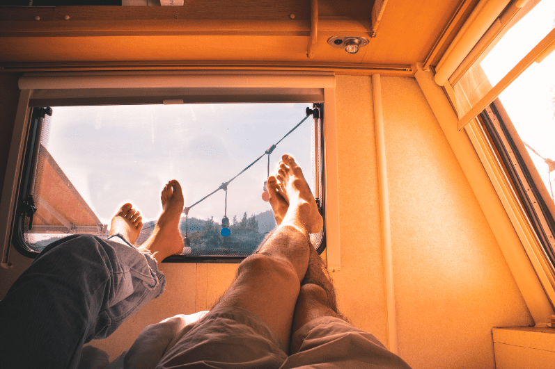 Two pairs of legs hanging out of the window of an RV on a trip to the Oregon Coast in Bandon