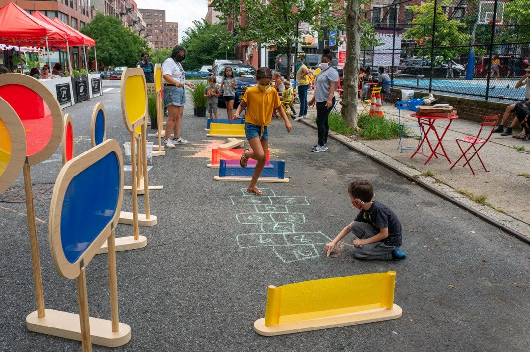 Neighborhood kids interact with an obstacle course set up onside on the street