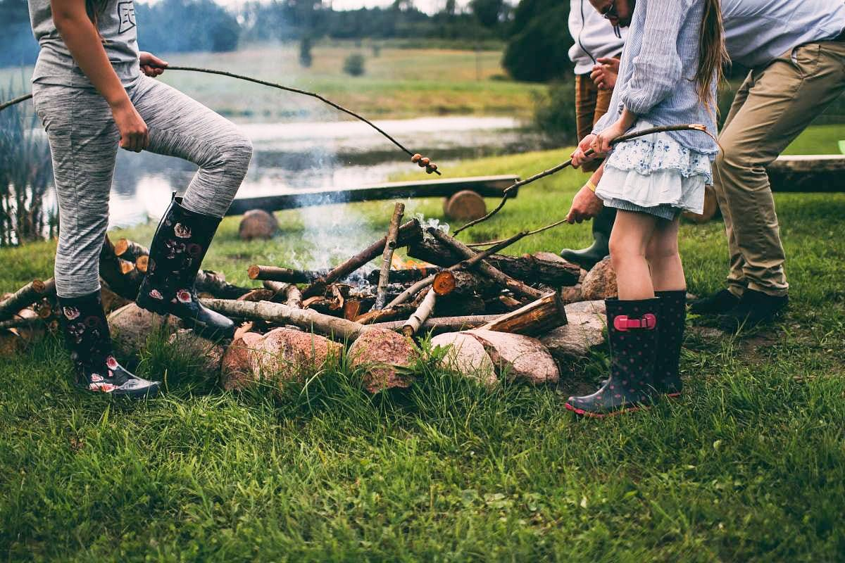 a family gathers together by the campfire to cook hotdogs on their family rv camping trip
