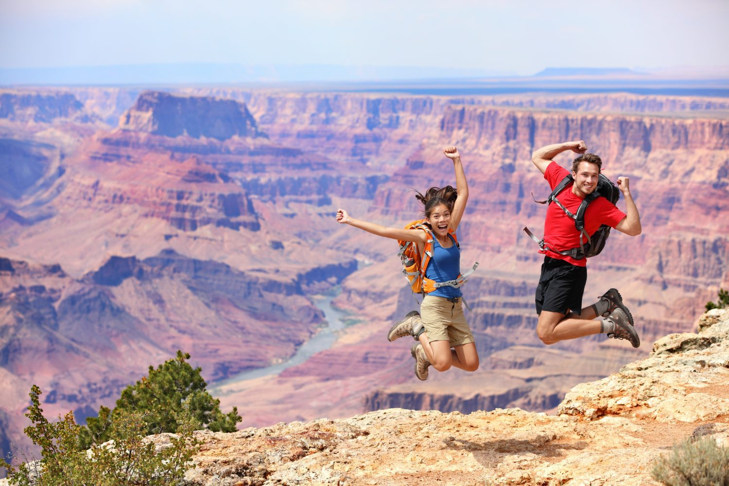 Happy people jumping in Grand Canyon. Young multiethnic couple on hiking travel. Grand Canyon, south rim, Arizona, USA.