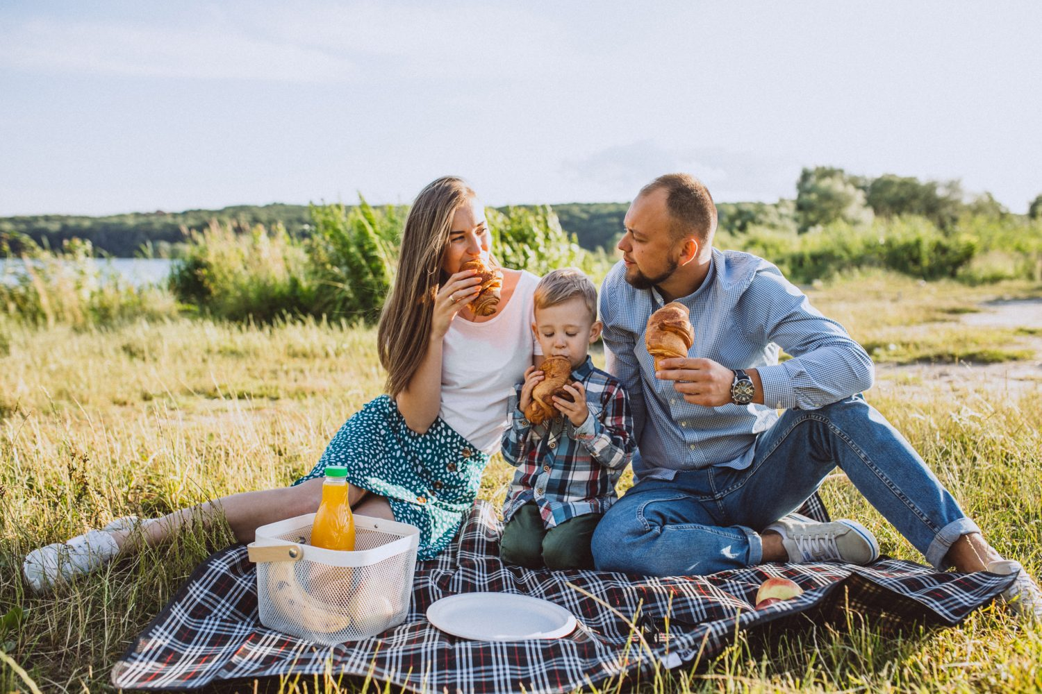 Two young parents eat at a picnic with their toddler